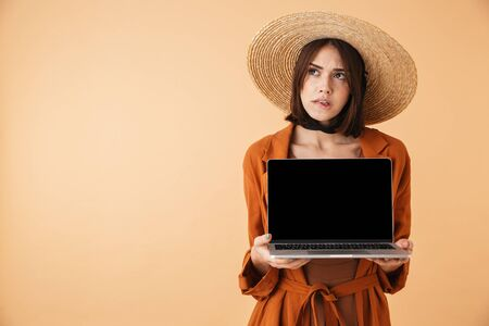 Beautiful pensive young woman wearing straw hat standing isolated over beige background, showing blank screen laptop computer