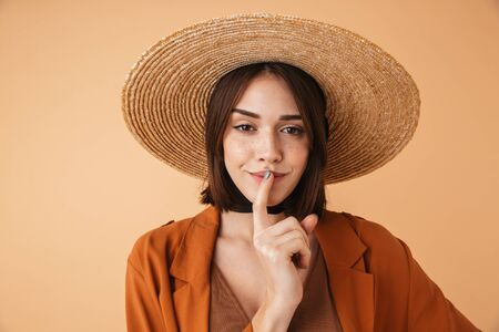 Portrait of a beautiful young woman wearing straw hat standing isolated over beige background, showing silence gesture Zdjęcie Seryjne