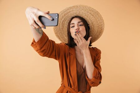 Beautiful young woman wearing straw hat standing isolated over beige background, taking a selfie, sending kiss