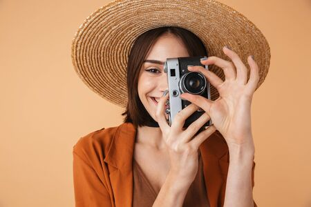 Beautiful young woman wearing straw hat and summer outfit standing isolated over beige background, taking pictures with photo camera