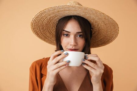Beautiful young woman wearing straw hat and summer outfit standing isolated over beige background, holding a cup