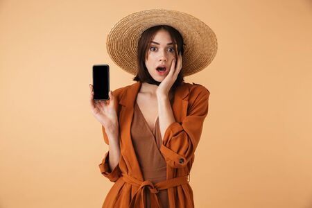 Beautiful smiling young woman wearing straw hat standing isolated over beige background, showing blank screen mobile phone