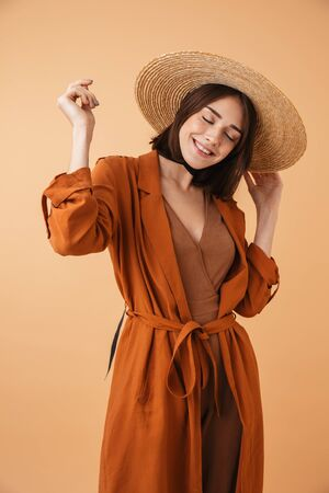 Portrait of a beautiful young woman wearing straw hat standing isolated over beige background, posing Zdjęcie Seryjne