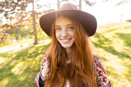Image of optimistic cheerful smiling happy young student redhead girl in autumn park walking.