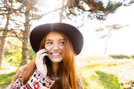 Photo of a happy pleased cutie young student redhead girl in autumn park talking by mobile phone. 写真素材