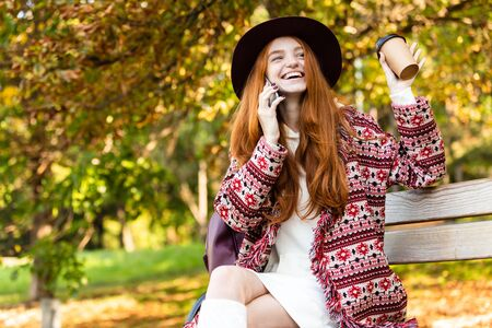 Image of a positive cheery young student redhead girl in autumn park talking by mobile phone drinking coffee waving to friends. 写真素材