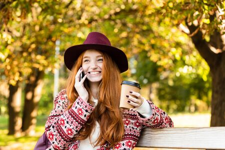 Image of a positive pleased laughing young student redhead girl in autumn park talking by mobile phone drinking coffee.