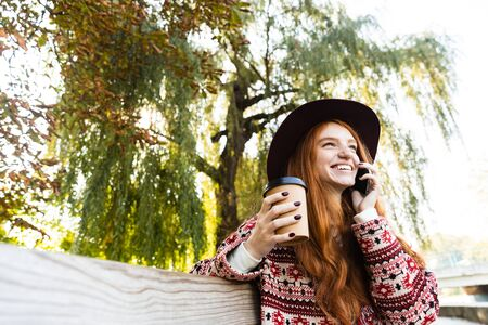 Image of a positive pleased happy cheery young student redhead girl in autumn park talking by mobile phone drinking coffee.