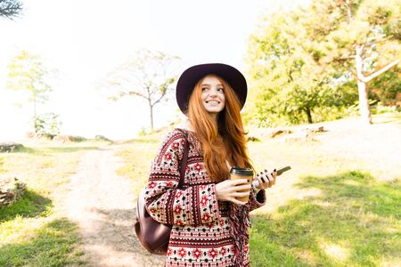 Image of a cute positive young student redhead girl in autumn park using mobile phone. 写真素材