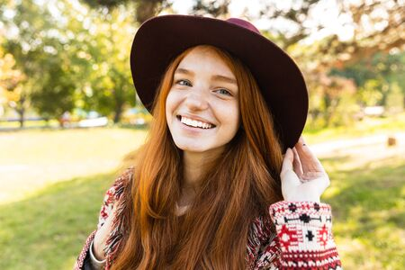Portrait of optimistic cheerful smiling happy young student redhead girl in autumn park walking.