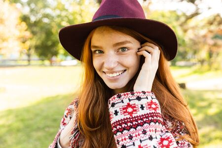 Image of smiling cheerful young student redhead girl in autumn park walking.
