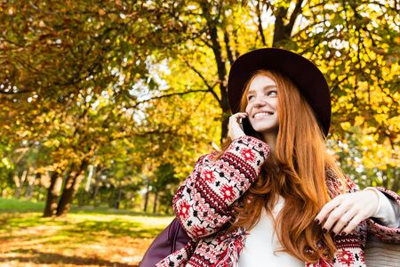 Photo of a positive cutie young student redhead girl in autumn park using mobile phone talking. 写真素材