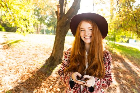 Image of a happy positive cutie young student redhead girl in autumn park using mobile phone. 写真素材