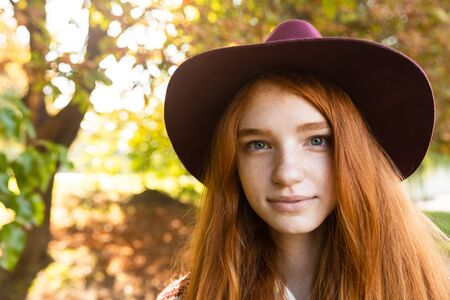 Image of positive cheerful happy young student redhead girl in autumn park walking. 写真素材