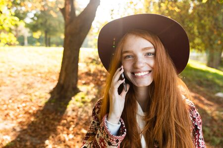 Picture of a smiling pleased cutie young student redhead girl in autumn park using mobile phone talking. 写真素材