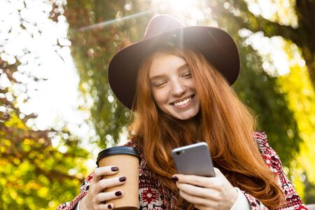 Image of a happy young student redhead girl in autumn park using mobile phone drinking coffee.