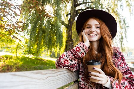 Image of a positive smiling happy young student redhead girl in autumn park drinking coffee. 写真素材