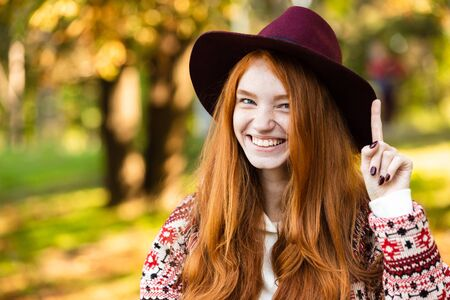 Photo of a smiling cute young student redhead girl in autumn park using mobile phone sit on bench wearing hat.