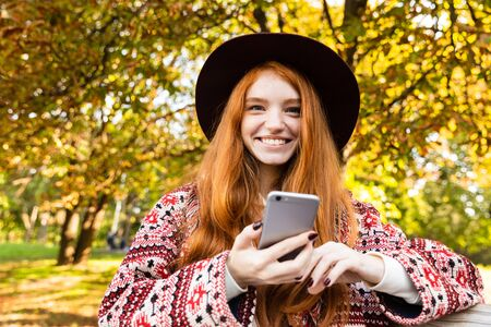 Photo of a smiling cheery young student redhead girl in autumn park using mobile phone sit on bench. 写真素材