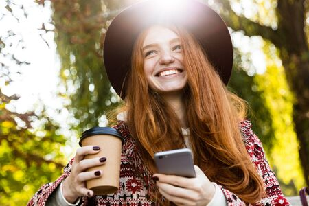 Image of a smiling cheery young student redhead girl in autumn park using mobile phone drinking coffee. 写真素材