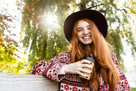 Image of a positive pleased young student redhead girl in autumn park drinking coffee.