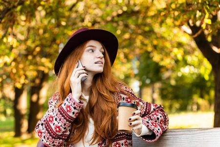 Image of a concentrated young student redhead girl in autumn park talking by mobile phone drinking coffee.