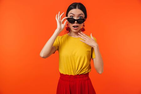 Image of cheerful hispanic woman 20s wearing sunglasses smiling at camera isolated over red background 写真素材