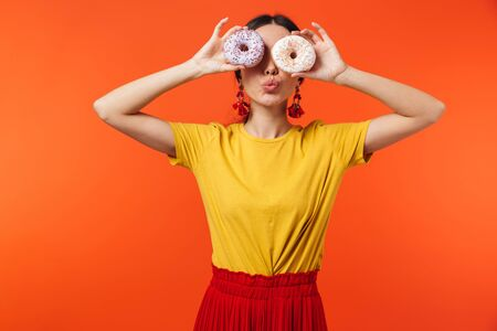Image of brunette hispanic woman 20s dressed in skirt smiling and holding two sweet donuts isolated over red background 写真素材