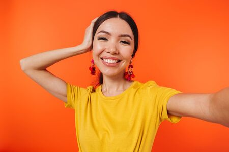 Image of pleased hispanic woman 20s dressed in skirt laughing at camera while taking selfie photo isolated over red background