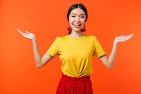 Image of pretty hispanic woman 20s dressed in skirt throwing up hands isolated over red background 写真素材