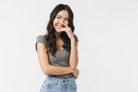 Image of gorgeous brunette woman 20s dressed in basic clothes smiling at camera isolated over white background