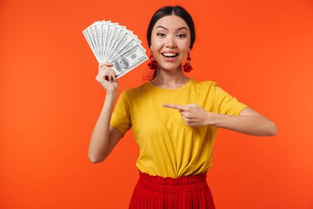 Image of young hispanic woman 20s dressed in skirt smiling while holding bunch of money bills isolated over red background 写真素材