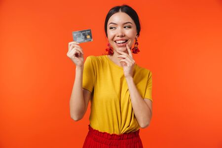 Image of brunette hispanic woman 20s dressed in skirt smiling and holding credit card isolated over red background 写真素材