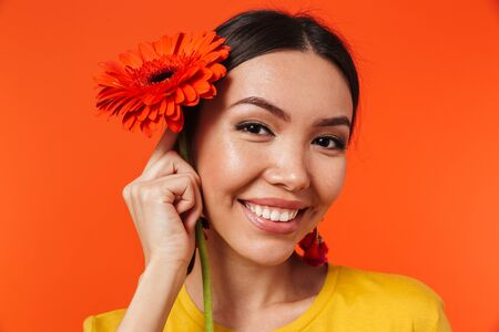 Image of a beautiful happy young woman posing isolated over orange wall background holding flower.