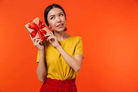 Image of a beautiful young woman posing isolated over orange wall background holding present box.