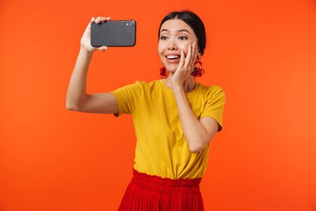 Image of a beautiful happy young woman posing isolated over orange wall background talking by mobile phone take a selfie. Stok Fotoğraf