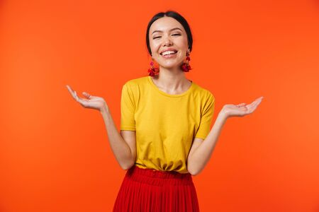 Image of a beautiful excited happy young woman posing isolated over orange wall background showing copyspace. Stok Fotoğraf