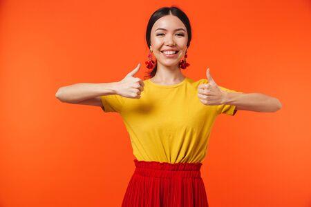 Image d'une belle jeune femme heureuse excitée posant isolée sur fond de mur orange faire un geste de pouce vers le haut. Banque d'images