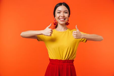Image of a beautiful excited happy young woman posing isolated over orange wall background make thumbs up gesture. Foto de archivo