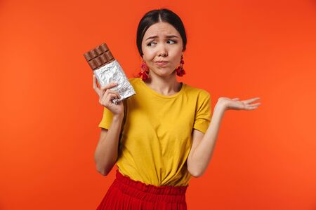 Image of doubtful hispanic woman 20s dressed in skirt holding chocolate bar isolated over red background
