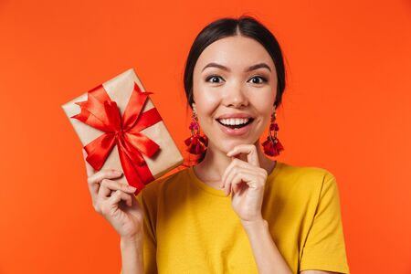 Image of a beautiful excited young woman posing isolated over orange wall background holding present box.