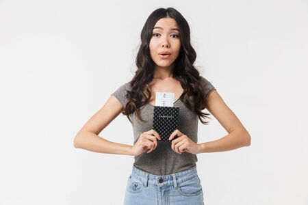 Image of a beautiful excited happy young woman posing isolated over white wall background holding passport with tickets.