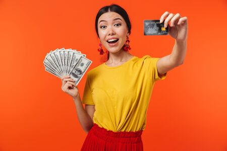 Image of elegant hispanic woman 20s dressed in skirt smiling while holding cash money and credit card isolated over red background