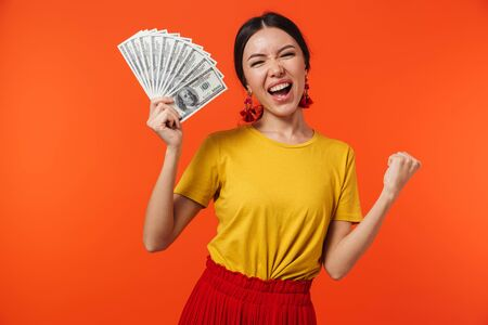 Image of beautiful hispanic woman 20s dressed in skirt smiling while holding bunch of money bills isolated over red background