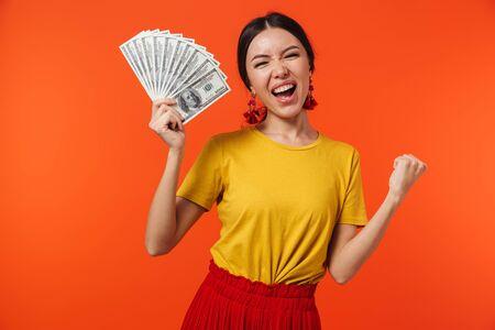 Imagen de hermosa mujer hispana de 20 años vestida con falda sonriendo mientras sostiene un montón de billetes de dinero aislado sobre fondo rojo.