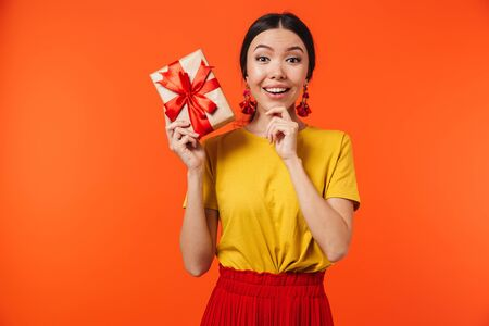 Image of gorgeous hispanic woman 20s dressed in skirt smiling and holding birthday present with bow isolated over red background Stok Fotoğraf