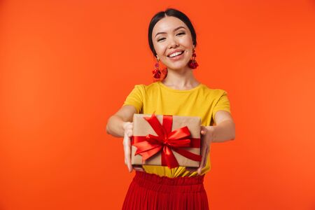 Image of happy hispanic woman 20s dressed in skirt smiling and holding birthday present with bow isolated over red background