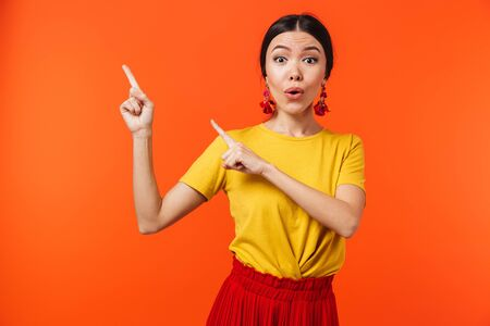 Image of a beautiful excited shocked young woman posing isolated over orange wall background pointing.