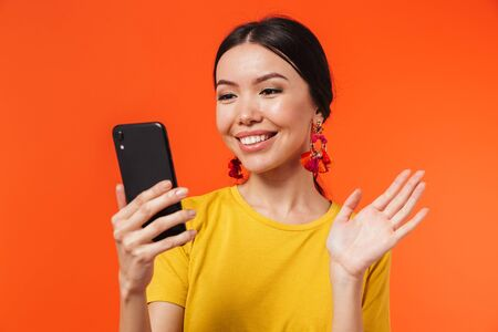 Image of a beautiful happy young woman posing isolated over orange wall background talking by mobile phone take a selfie waving.