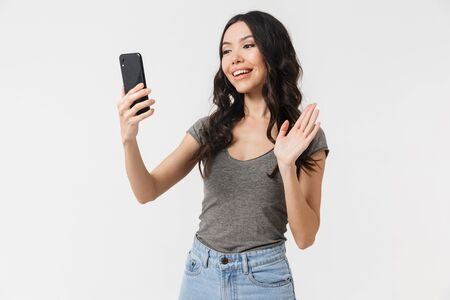 Image of young brunette woman 20s dressed in basic clothes smiling and looking at mobile phone isolated over white background